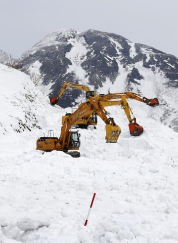 冬季通行止めとなっている知床横断道路の除雪作業。奥は羅臼岳=6日、北海道羅臼町