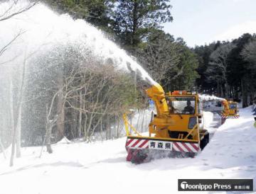 雪を高く飛ばし恐山街道を除雪するロータリー車