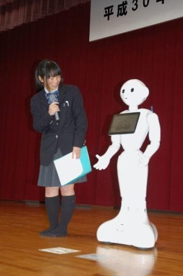 【ペッパーと対話する勝田副会長(左)=鈴鹿市庄野町の鈴鹿高校で】