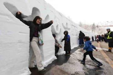 雪壁のくぼみに入って記念撮影する人たち(岩崎勝撮影)