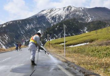 志賀草津道路の火山灰を洗い流す作業員。奥は噴火した本白根山=12日、群馬県草津町