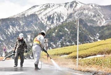 火山灰がうっすらと積もった道路を洗浄する作業員。後ろに見えるのは噴火のあった本白根山=12日午前11時半ごろ、草津町の志賀草津道路(国道292号)