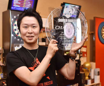 チャンピオンに贈られる盾を手に笑顔の村松治樹さん
