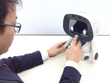 ロボット「ユニボ」の設定をする日本PCサービスの社員=吹田市