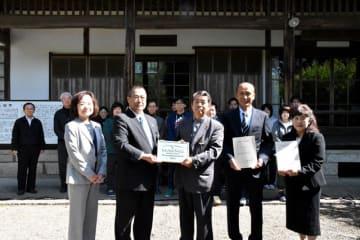 文化財プレートを贈呈した木城町の半渡町長(左から2人目)と児嶋理事長(左から3人目)