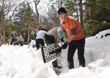 スコップを手に残雪と格闘する参加者たち