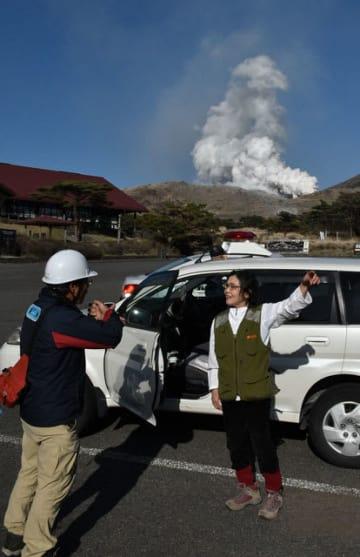 霧島連山・硫黄山が噴火し、えびのエコミュージアムセンター駐車場で職員から避難の誘導を受ける登山客(右)=19日午後4時50分、えびの市・えびの高原
