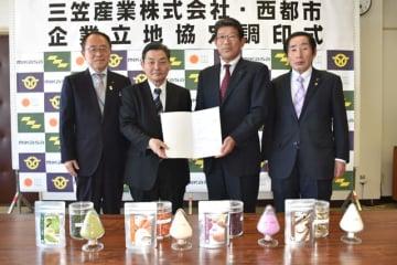 加工場新設に関する調印式を終え、製品の前で記念撮影する押川市長(右から2人目)、佐伯社長(同3人目)ら