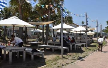オープンしたばかりの青島ビーチパークに足を運び、食事や会話を楽しむ観光客ら