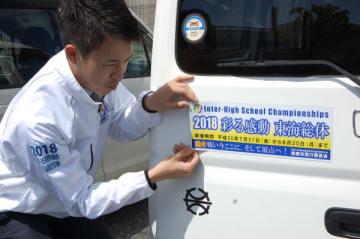 【公用車に高校総体PR用ステッカーを貼る市職員=鈴鹿市役所公用車駐車場で】