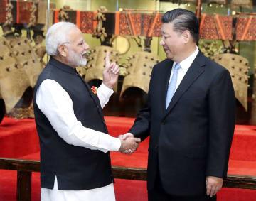 インドのモディ首相(左)と握手する中国の習近平国家主席=27日、中国湖北省武漢(新華社=共同)