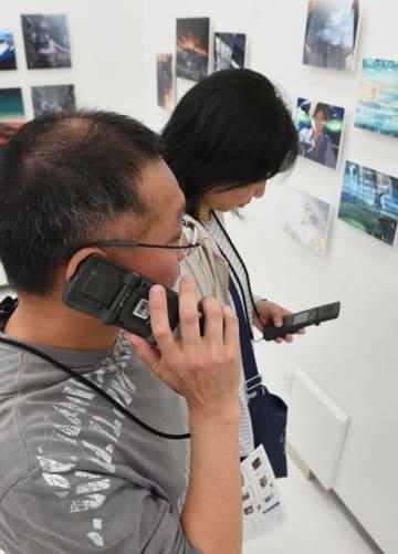 携帯電話型の音声ガイド機に番号を入力すると、神木さんの声による映画の紹介などが流れる=宮崎市・みやざきアートセンター