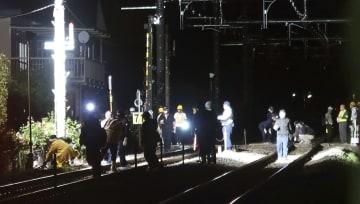 電動車椅子に乗った女性がはねられたJR中央線の踏切周辺を調べる警察官ら=3日午後9時35分ごろ、山梨県山梨市
