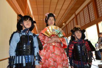 打掛と甲冑(かっちゅう)を着てポーズを取る子ども=佐賀市の佐賀城本丸歴史館