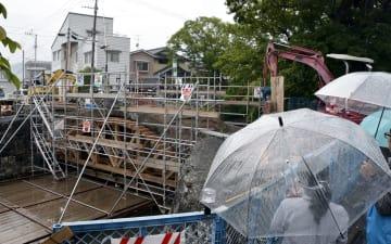 解体工事が進む船場橋で開かれた現地説明会。雨の中、市内外の約80人が参加した=宇土市