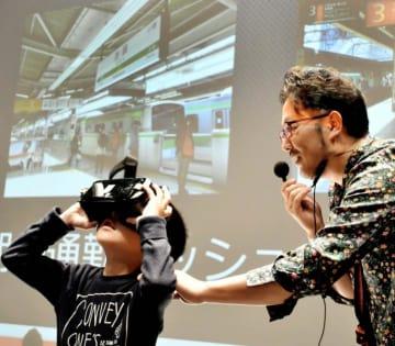 原さん(右)が最新の映像技術を紹介したワークショップでVRを体験する子ども