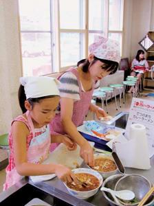 最優秀賞に輝いた「てつのまちカレーラーメン」を一生懸命に調理する松本さん親子