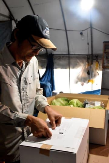 レタスを詰めた箱にQRコード付きのシールを貼る生産農家