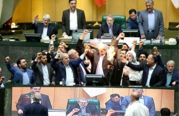 9日、テヘランの国会議事堂でトランプ米大統領に抗議し、核合意の条文が記された資料と星条旗を燃やす国会議員ら(イラン国会提供・共同)