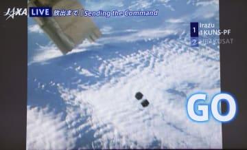 国際宇宙ステーションの日本実験棟「きぼう」から宇宙空間に放出された、ケニアとコスタリカの超小型衛星の中継映像=11日夜、茨城県つくば市のJAXA筑波宇宙センター