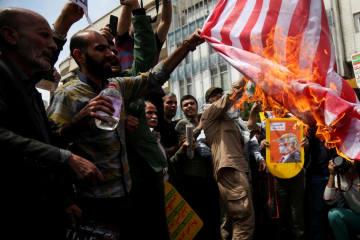 11日、テヘランで行われたデモで星条旗に火を放つ参加者(ロイター=共同)