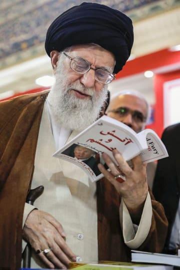 トランプ米政権の暴露本「炎と怒り」を手に取るイランの最高指導者ハメネイ師=11日、テヘラン(イラン最高指導者事務所提供・共同)