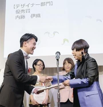 コシノジュンコさんから表彰式を受け取る内藤さん