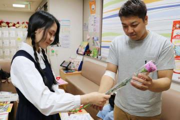 カーネーションを受け取る献血協力者(右)=長崎市、献血ルーム「はまのまち」