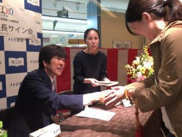 著書を購入したファンと握手する高田社長(左)=長崎市、メトロ書店本店