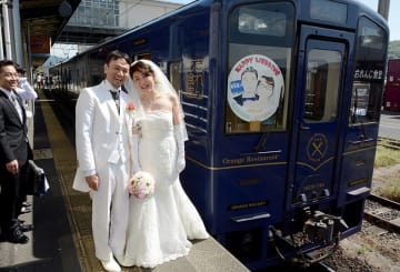 観光列車「おれんじ食堂」で結婚披露宴を開いた川村雅紀さん、美由紀さん夫妻。列車のヘッドマークには2人の似顔絵が描かれている=鹿児島県薩摩川内市