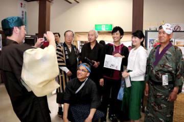侍などに仮装した住民らと記念撮影する観光客(近江八幡市為心町元・白雲館)