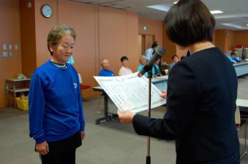【末松市長から完歩の満願表彰を受ける受賞者(左)=鈴鹿市役所で】