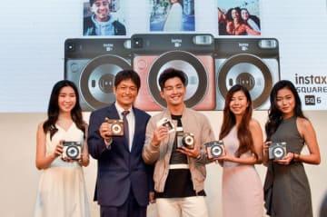 カジュアルなデザインの「instax スクエアSQ6」を手にするフジフイルム(マレーシア)の中村マネジング・ディレクター(左から2人目)やアルヴィン・チョンさん(中央)ら=15日、クアラルンプール(NNA撮影)