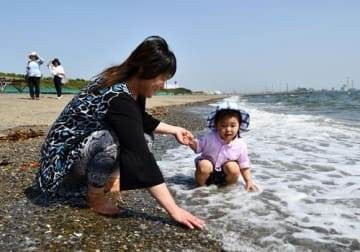 波打ち際で戯れる親子=15日午後2時10分ごろ、千葉市美浜区のいなげの浜