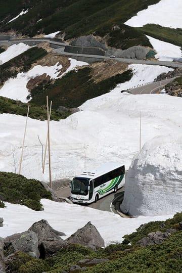 全線開通した乗鞍スカイラインで、雪の壁の間を縫って進むバス=岐阜県高山市丹生川町