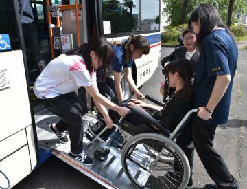 車椅子でバスの乗降体験をする学生たち=水戸市文京