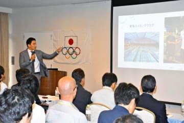 五輪競技の強化担当者らに、本県の魅力などを説明する松田丈志さん=17日午後、宮崎市のコテージ・ヒムカ