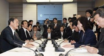首相官邸で開かれた人身取引対策推進会議の会合であいさつする菅官房長官(左端)=18日午前