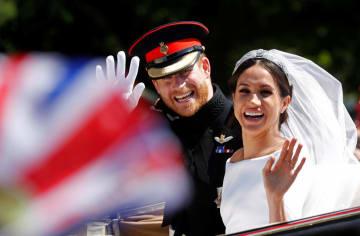 19日、ロンドン郊外ウィンザーで結婚式後のパレードで手を振るヘンリー英王子(左)とメーガン妃(ロイター=共同)