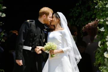 19日、ロンドン郊外ウィンザーで結婚式後にキスをするヘンリー英王子(左)とメーガン妃(ロイター=共同)