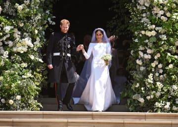 19日、結婚式が執り行われたロンドン郊外のウィンザー城の聖ジョージ礼拝堂から出るヘンリー英王子(左)とメーガン妃(UPI=共同)