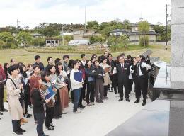 宮城県東松島市野蒜地区の慰霊碑の前で佐々木課長(右)らの説明を聞く受講生