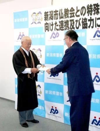県警からの要請書を受け取る市仏教会の小林一三会長(左)=21日、新潟市中央区