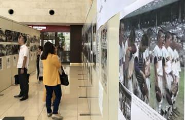 戦後の沖縄の写真に見入る来場者ら=23日、那覇市久茂地のタイムスビル