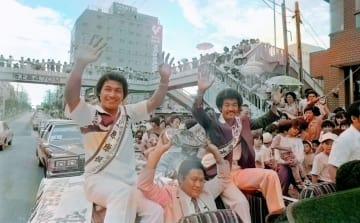 WBA世界ジュニアフライ級・具志堅用高、同ライト級・上原康恒の両王者が那覇市内を凱旋パレードした=1980年8月9日、国際通り(ニューラルネットワークによる自動色付け)