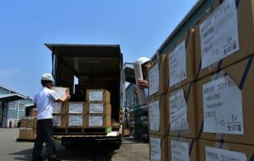 トンガに送るランドセルが入った段ボール箱をトラックから積み下ろす海老名市教育委員会の担当者ら=横浜市中区の山下ふ頭