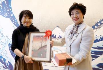 5万人目の入場者となり、釜崎社長(右)から記念品を受け取る島崎さん=長崎市、県美術館