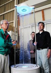 人気が高まっている「プリズムフォール」と、愛水工業を営む深水正社長(左)ら家族3人=神戸市西区櫨谷町寺谷
