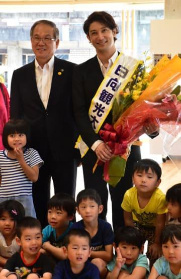 日向市観光大使の委嘱を受け、記念撮影に応じる西島さん(後列右)