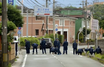 警察官による発砲があった現場付近で、弾丸を捜す捜査員=29日午前10時7分、熊本市東区